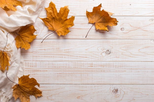 White scarf and dry yellow leaves on a wooden table. autumn background, copyspace.