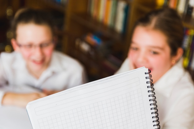 White school copybook and laughing little girls