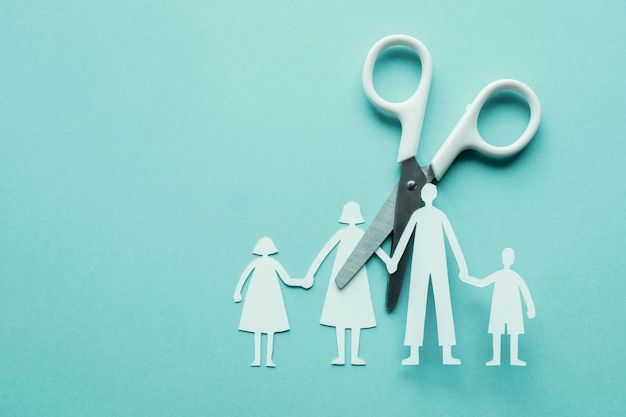 White scissor cutting family paper cut out on blue background