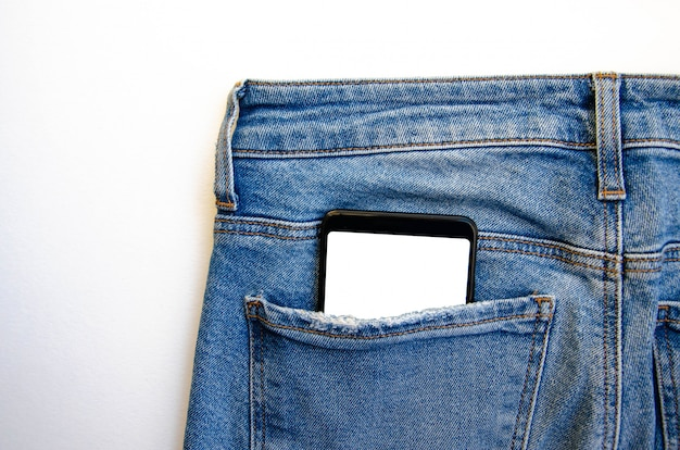 White screen smartphone in jeans pocket. smartphone place for text. smartphone in a pocket on a white table.