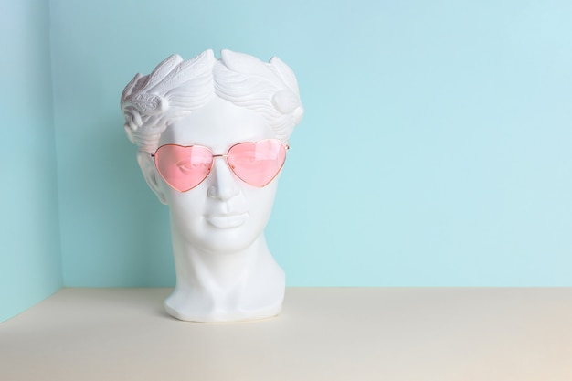 White sculpture of an antique head in pink glasses with hearts