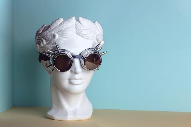 Белая скульптура античной головы в очках рок.