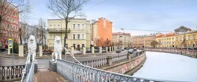 曇りの冬の日にサンクトペテルブルクのグリボエードフ運河に架かるライオンブリッジのライオンの白い彫刻
