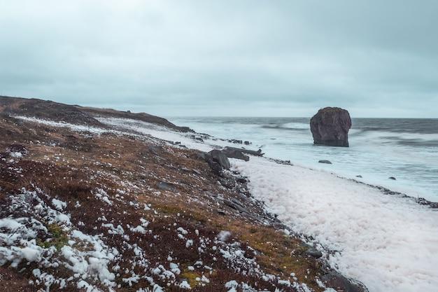海岸の白い海の泡。白海の嵐、岸に波が転がる劇的な風景。