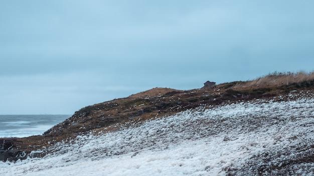 해안에 하얀 바다 거품입니다. 백해의 폭풍, 해안에 굴러가는 파도가 있는 극적인 풍경.