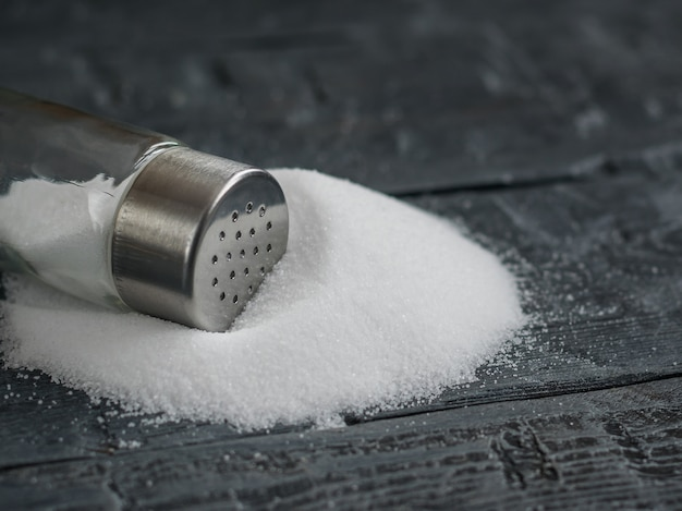 White sea salt fine ground is poured on the black wooden table