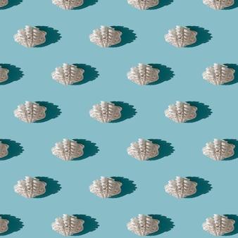 水色の背景にハードシャドウと白い貝殻のシームレスなパターン。夏の季節と海の休暇の概念。自然の背景
