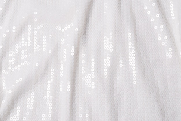 White sequin background. white shiny sequin fabric. top view.
