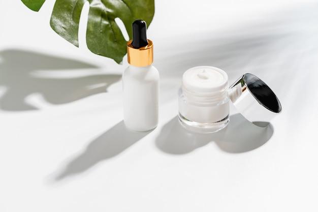 Бутылка с белой сывороткой и баночка с кремом, макет косметического бренда. вид сверху на белом фоне.