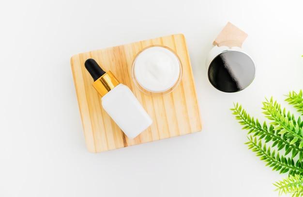 Белая бутылка с сывороткой и баночка с кремом