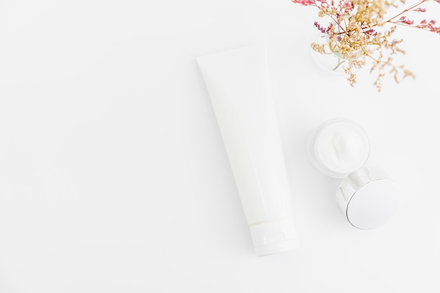 White serum bottle and cream jar, beauty product brand. top view