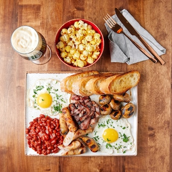 White set tray with food, sausages, bacon, beans, meatballs, scrambled eggs with greens, kvass, white toasted bread, beer in a glass goblet, bowl of popcorn