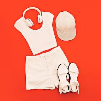 ホワイトセット。明るいピンクの背景に白い服やアクセサリー。都会的なスタイル