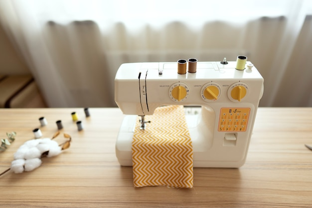 A white sewing machine stands on the table