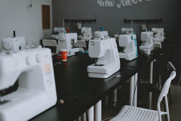 테이블에 흰색 재봉틀입니다. 재봉틀, 재단사 워크샵.