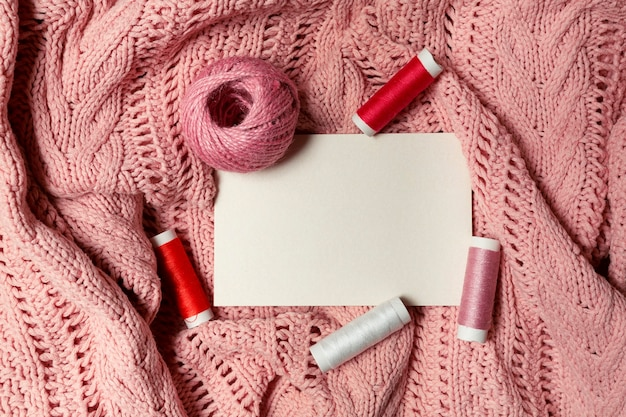 ピンクのニット生地に羊毛のボールと糸でテキストを挿入するための白いシーツ