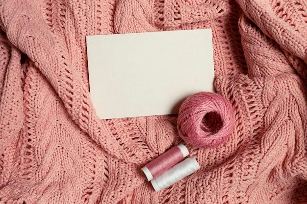 Белый лист для вставки текста с клубком шерсти и ниток на розовом трикотажном полотне