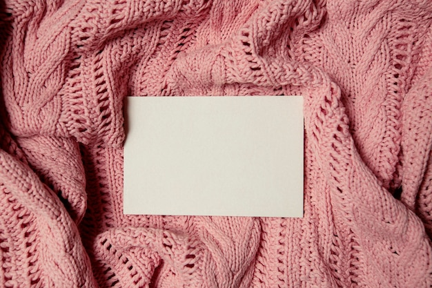 White sheet for inserting text with a ball of wool and threads on a pink knitted fabric