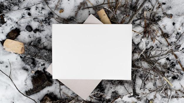 白いシーツのモックアップ。一枚の紙と雪と黒い石炭、上面図。テキスト用の空きスペース、フラットレイ。はがき、ブランディング