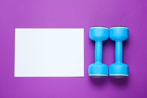 コピースペース、紫色のテーブルにプラスチックのダンベルの紙の白いシート。クリエイティブフィットネステーブル