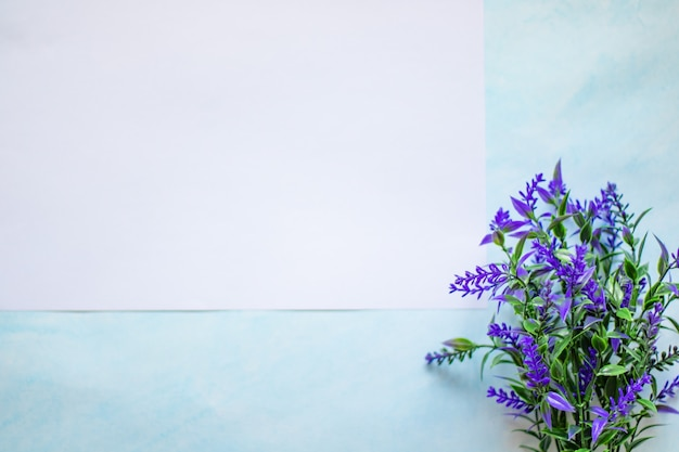 Белый лист бумаги на синем фоне с веточкой голубой лаванды место для текста