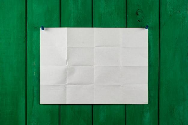 Белый лист бумаги на зеленом деревянном заборе.