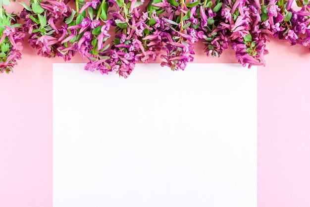Белый лист бумаги на розовом фоне с букетом розовых и фиолетовых цветов вид сверху