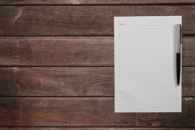 펜으로 나무 테이블 위에 하얀 시트