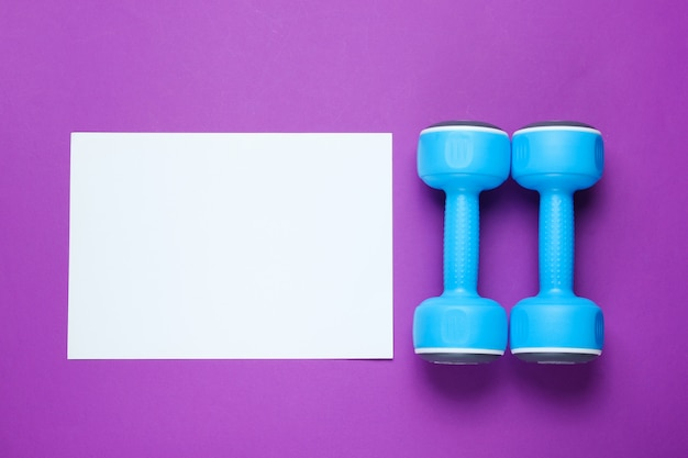 White sheet of paper for copy space, plastic dumbbells on purple table. creative fitness table