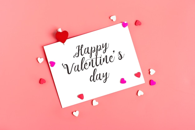White sheet of paper on pink background happy valentines day concept