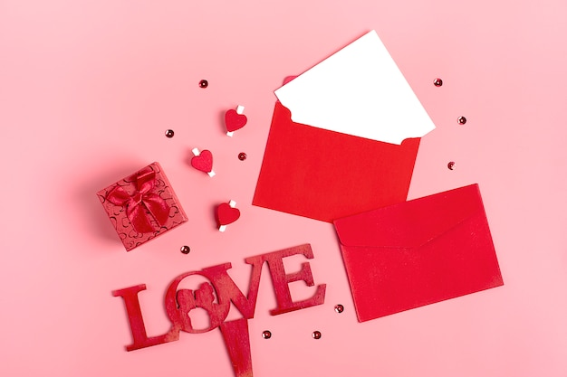 White sheet of paper, red envelope, gift box, tittle sparkles, pen on pink background