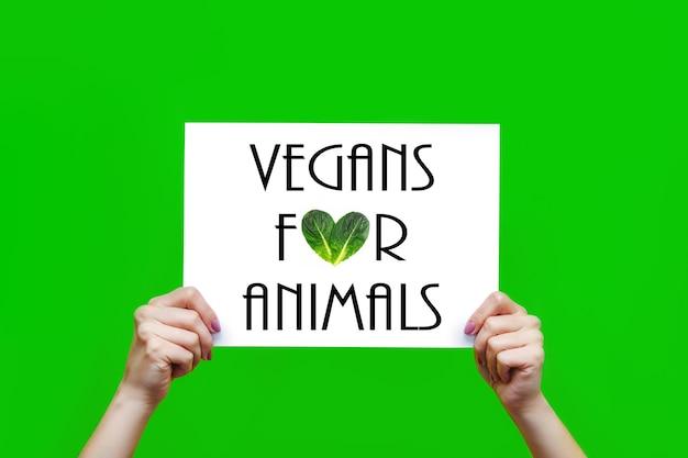 녹색 배경에 격리된 암컷 손에 동물을 위한 채식주의자라는 슬로건이 있는 흰색 시트