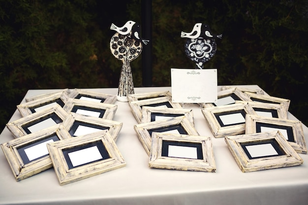 White sheets of paper in wooden photo frames lie on the table, and behind there is a birds decoration kissing