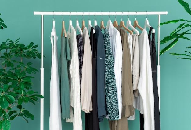 緑の大きな植物と緑の背景にたくさんの服が付いている白い棚。