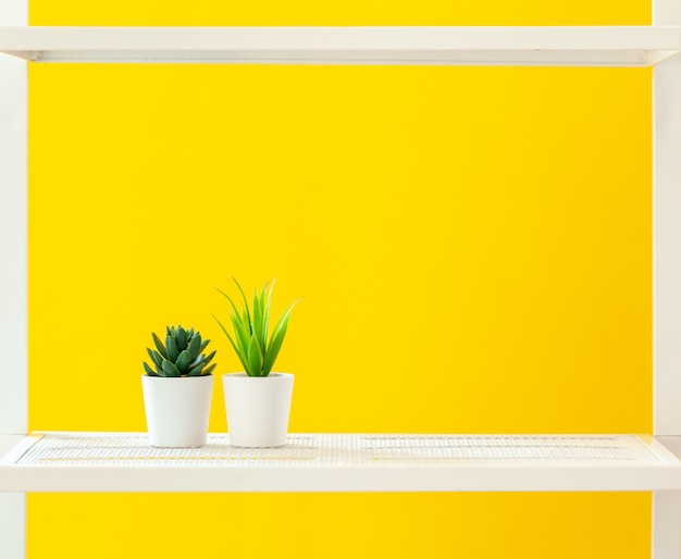 White shelf with stationery objects against bright yellow background
