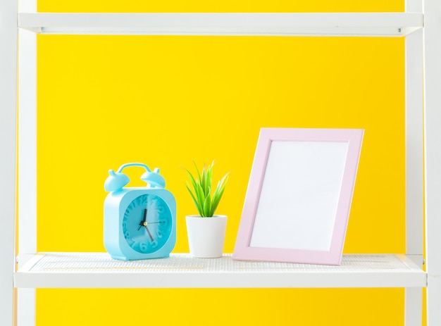 White shelf with stationery objects against bright yellow