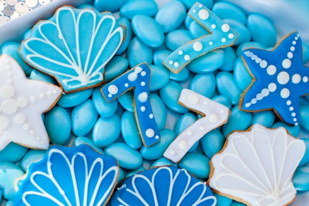 White shell plate full of chocolate candies with blue icing, cookies like shells, stars and number seven