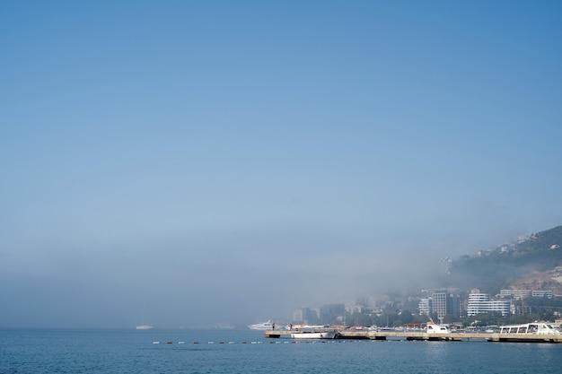하얀 배들은 안개 속에서 해안 근처의 부두에 서 있다