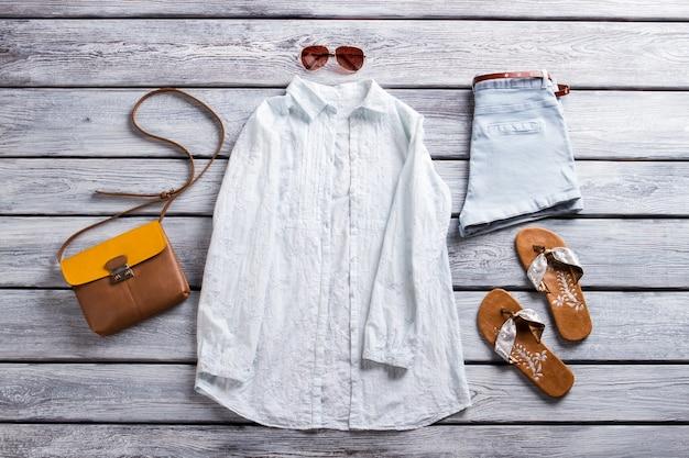 白いシャツと青いショートパンツ。カジュアルなシャツとビーチサンダル。ブティックショーケースの新しいサングラス。魅力的な夏の装い。