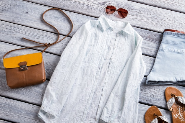 白いシャツとビーチサンダルの水色のショートパンツとバッグの女の子の亜麻のシャツが低価格で新しいアイテムを展示しています
