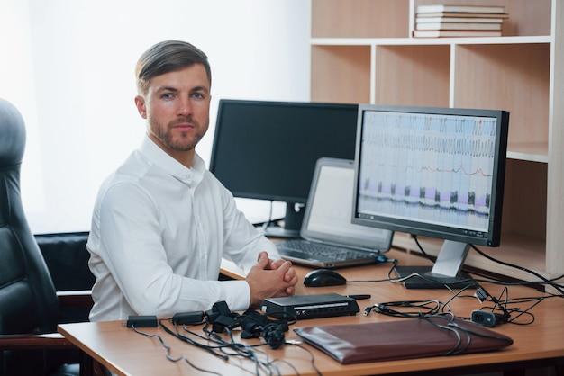 白いシャツと多くのデバイス。ポリグラフ検査官は彼の嘘発見器の機器を使用してオフィスで働いています