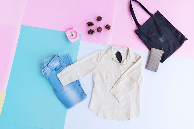 White shirt, blue jeans, brown purse and black bag on multi pastel color background