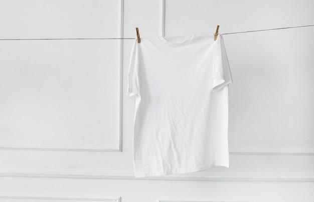 Белая рубашка висит у стены