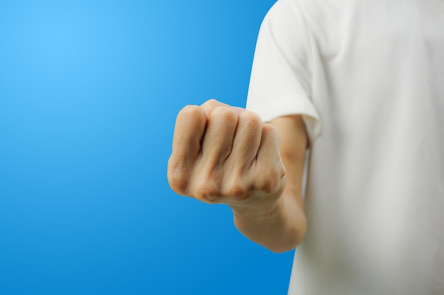 A white shirt man showing fist with his hand front view on blue background.