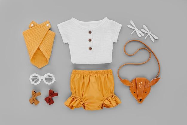 Белая рубашка, оранжевые шорты с детской сумочкой и солнцезащитные очки. набор детской одежды и аксессуаров для летних каникул на сером фоне. модная детская одежда. плоская планировка, вид сверху
