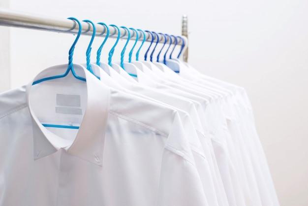 Белые рубашки висит на стойке в ряд