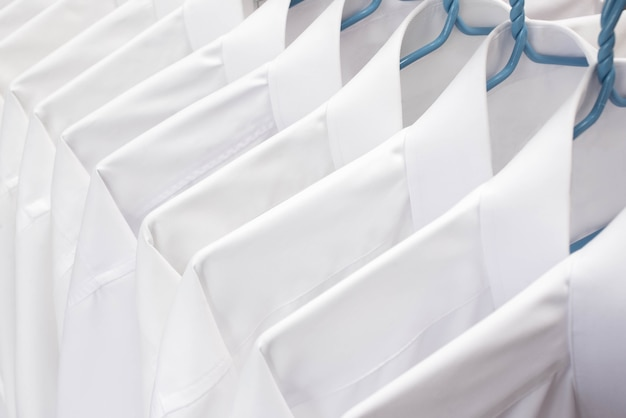 White shirts hanging on rack in a row