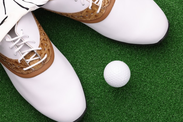White shoes and ball lying on green golf course closeup