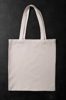디자인을 위한 흰색 쇼핑백 캔버스 천 에코 쇼핑 자루 모형, 복사 공간이 있는 검정색 질감 배경에 격리된 템플릿. 플랫 레이.
