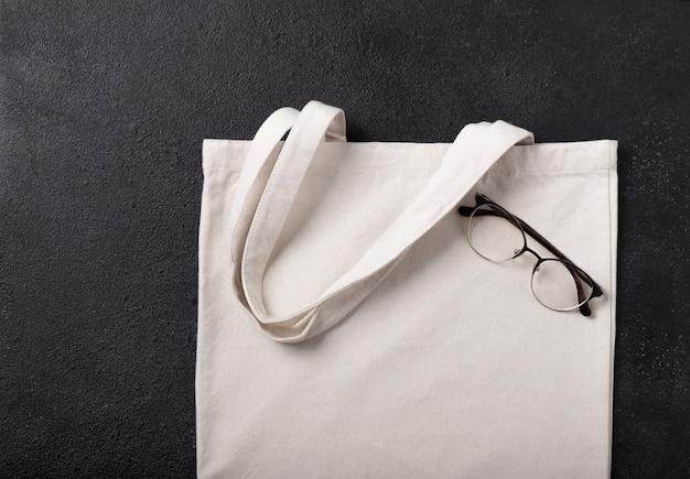 디자인을 위한 흰색 쇼핑백 캔버스 천 에코 쇼핑 자루 모형, 복사 공간이 있는 검정색 질감 배경에 격리된 템플릿. 안경. 플랫 레이.